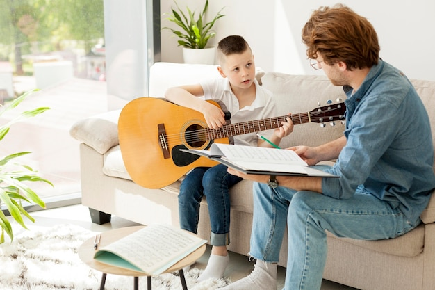 Tutor and boy learning guitar from home