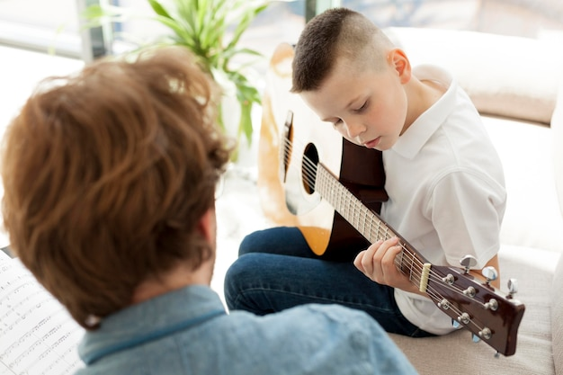 Tutor and boy learning guitar over the shoulder view