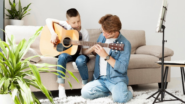 Tutor and boy learning how to play guitar long shot