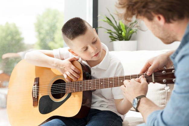 Tutor and boy playing guitar