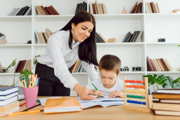 Tutor deals with the preschooler with a laptop, a real home interior, the concept of childhood and learning