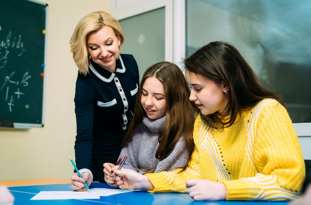 Tutor of english explaining lesson to two girls in class. school and education.