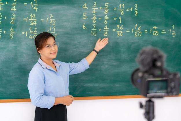 Репетитор объясняет математику на доске, проводя удаленный школьный урок онлайн