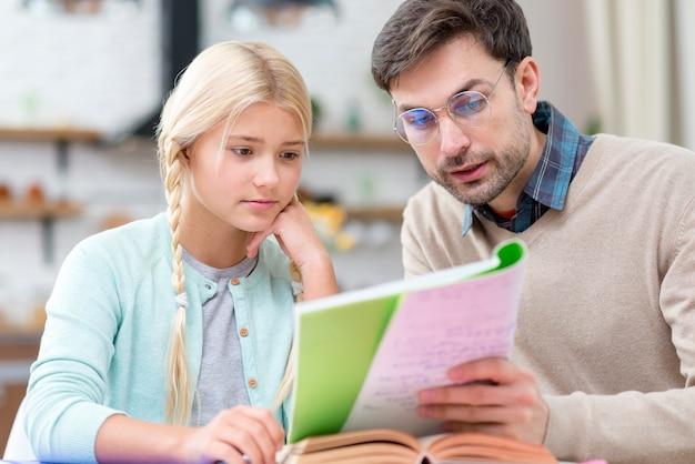 Tutor e ragazza a casa leggendo dal taccuino