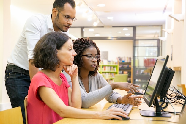 Tutor helping students in computer class