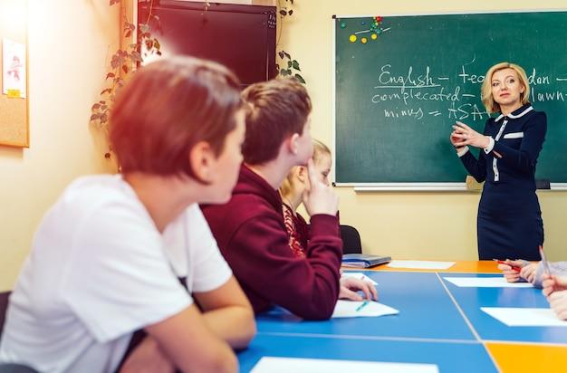 ホワイトボードの前に立っている家庭教師。笑顔の先生、黒板の近くの講師。聞いて勉強している生徒。