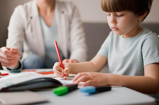 Tutor che insegna al bambino a casa
