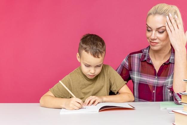 Репетитор с ребенком вместе делать домашнее задание дома.