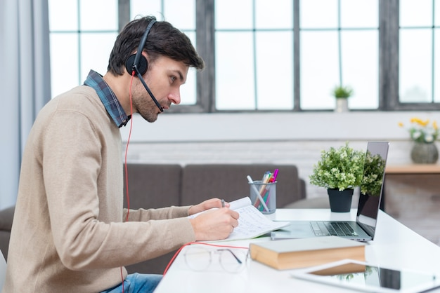 Tutor with headphones having an online meeting