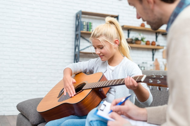 Tutor and young student learning how to play guitar
