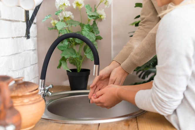 Tutor and young student washing their hands