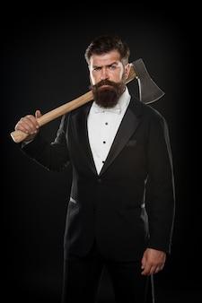 Босс вечеринки в смокинге. жестокий человек hispter держит топор на черном фоне. уверенный деловой костюм бизнесмена. серьезный мужской парикмахер с топором. парикмахерская. смокинг мужчина с бородой. стрижка усов острым лезвием.