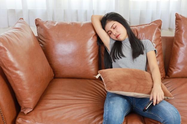 Tv와 행복 개념입니다. 거실 소파에서 캐주얼하게 잠을 자는 아름다운 아시아 여성, 텔레비전 리모컨을 들고 행복한 웃는 얼굴로 텔레비전을 보면서 잠을 자고 있습니다. 라이프 스타일 개념입니다.