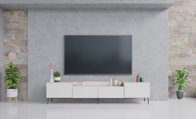 Tv on cabinet in modern living room with lamp, table, flower and plant on cement wall.