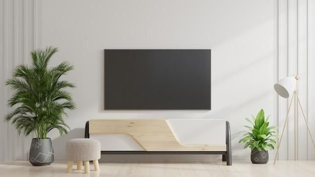在内阁的电视在有植物的现代客厅有在白色墙壁背景的。