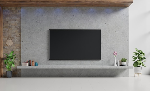 Tv on cement stan in modern living room with lamp,table,flower and plant on cement wall.
