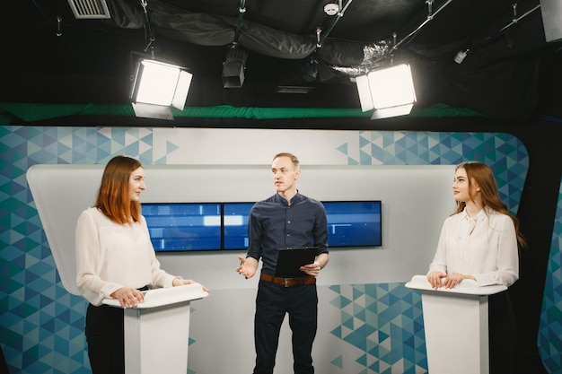 Tv game show with two participants answering questions or solving puzzles and host. smiling women participate in television quiz.