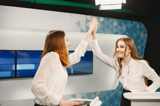 Телешоу с двумя участниками на трибунах. возбужденные женщины в телестудии, съемки телешоу.