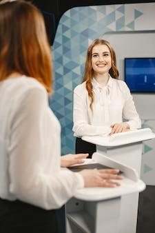 Tribunes に 2 人の参加者が立っているテレビ ゲーム ショー。テレビ スタジオで興奮した女性がテレビ番組を撮影しています。