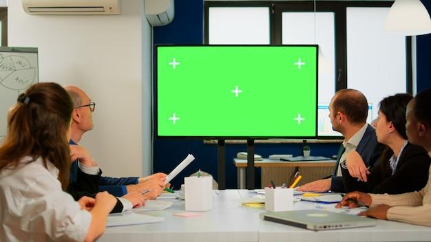 ビジネスマンが広い部屋で働いている間、机の前に置かれたプレゼンテーションの準備ができているテレビの緑色の画面のモックアップ。モックアップディスプレイモニターを備えたデジタルクロマキーインタラクティブホワイトボードを使用している従業員