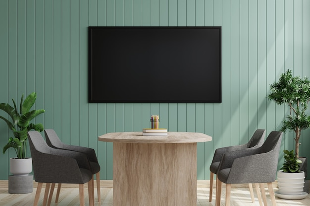 Tv on a green wooden wall in a conference room with chairs and desk