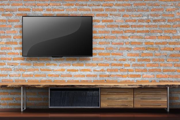 거실에 빈 나무 테이블 미디어 가구와 붉은 벽돌 벽에 tv