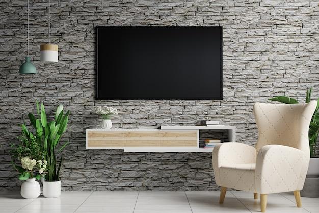 リビングルームの灰色のレンガの壁にテレビがあり、側面にランプがぶら下がっていて、アームチェアと植木鉢で飾られています
