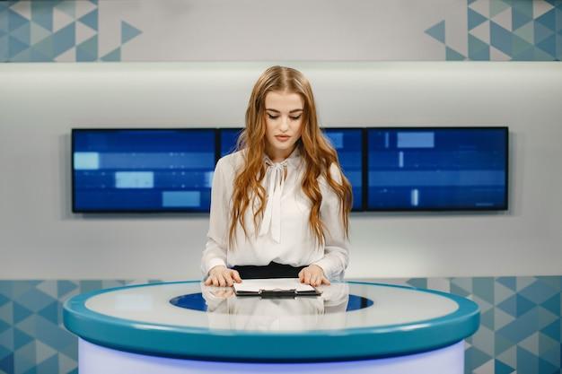 새로운 방송을 준비하는 스튜디오에있는 tv. 테이블에 앉아 흰 셔츠에 웃는 소녀.