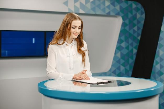 Телевидение в студии готовится к выходу в эфир. улыбающаяся девушка в белой рубашке, сидя за столом.