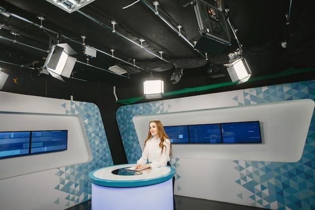 Tv presente in studio in preparazione per nuove trasmissioni. ragazza sorridente in camicia bianca seduta al tavolo.