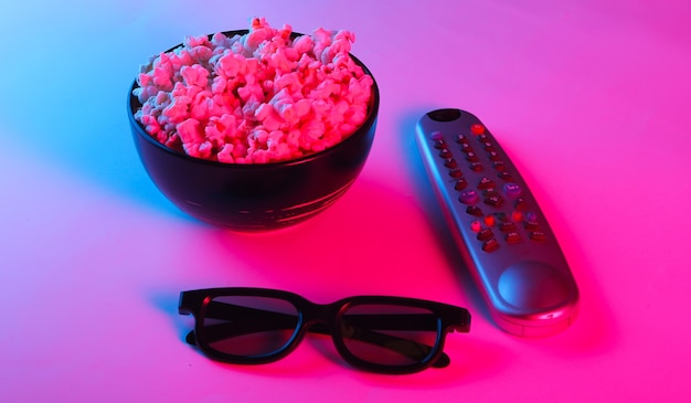 Tv remote, 3d glasses and a bowl of popcorn