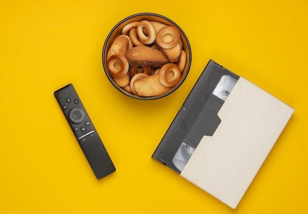 Tv 리모컨 및 크래커 그릇, 노란색 비디오 카세트.