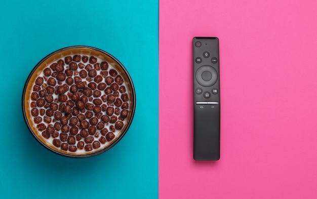 핑크 블루 그릇에 우유와 함께 tv 원격 제어 및 초콜릿 시리얼 공