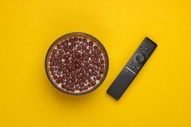노란색 그릇에 우유와 함께 tv 원격 제어 및 초콜릿 시리얼 공.