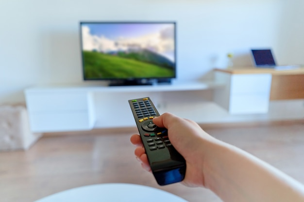 Tv remote control in hand to switch channels close up