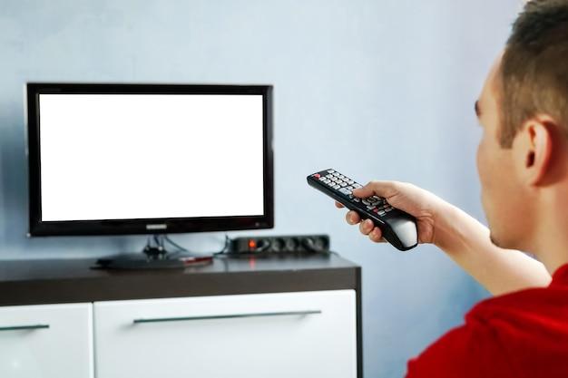 파란색 벽 배경에 빈 화면이 있는 와이드스크린 tv 앞에 있는 남성의 손에 있는 tv 리모컨. 젊은 남자는 tv에서 리모컨으로 채널을 전환합니다.