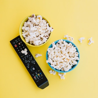 Tv remote control near bowls with popcorn