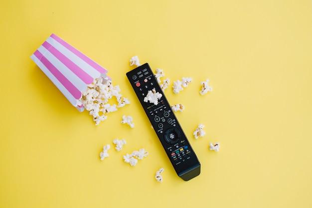 Tv remote control near spilled popcorn