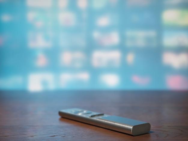 Пульт дистанционного управления телевизором на фоне экрана телевизора