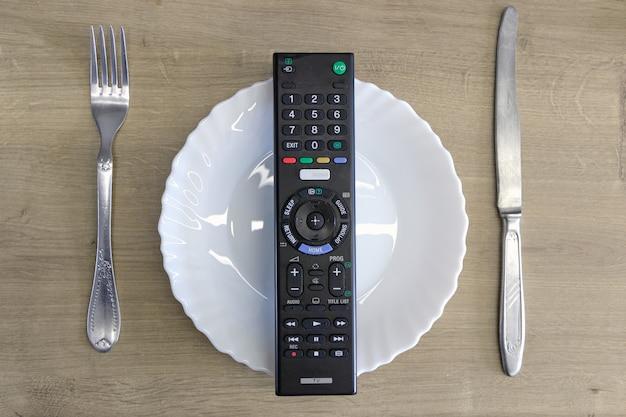 Пульт от телевизора на тарелке со столовыми приборами