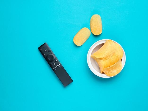 Тв пульт, картофельные чипсы в тарелку на столе. смотреть телевизор, вид сверху