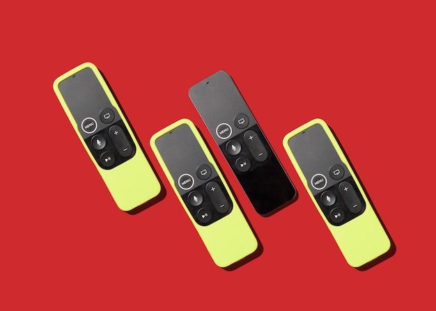 Телевизионные пульты в обложках на красном фоне