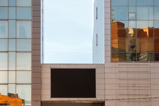 비즈니스 건물에 tv 화면입니다. tv 레이아웃 빌보드의 큰 빈 검은 화면. 현대적인 건물의 벽에 광고를 배치하기 위한 템플릿입니다. 건물에 빈 대형 빌보드 블랙 led 스크린