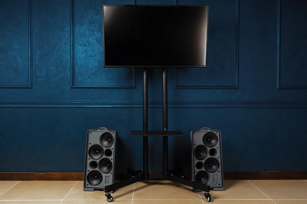 어두운 파란색 벽에 금속 스탠드에 tv