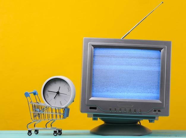 Tv 가게. 노란색에 시계와 안테나 구식 복고풍 tv 및 미니 슈퍼마켓 트롤리