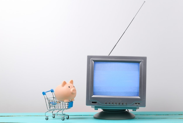Tv shop. antenna old-fashioned retro tv and mini supermarket trolley with piggy bank on white wall