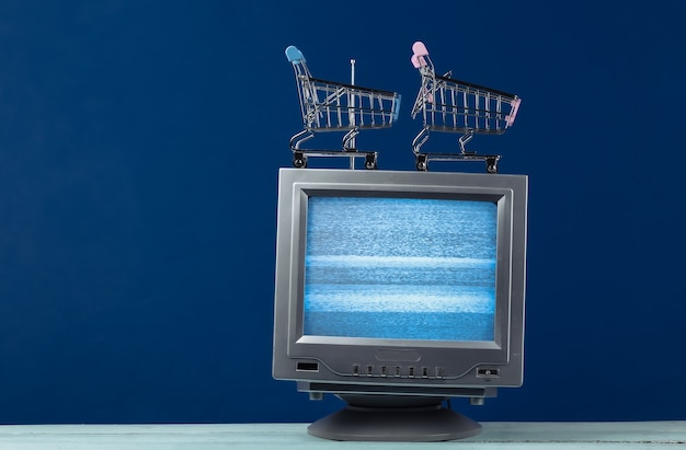 Tv shop. antenna old-fashioned retro tv with mini supermarket trolley on classic blue