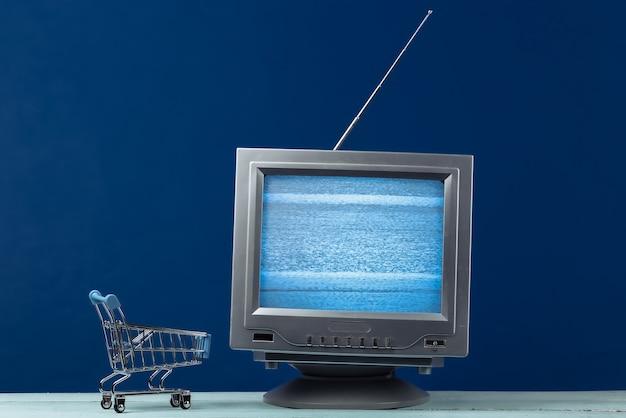 Tv 가게. 클래식 블루에 미니 슈퍼마켓 트롤리가있는 안테나 구식 복고풍 tv