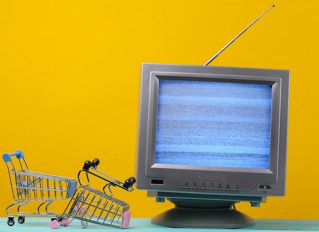 Tv 가게. 노란색에 미니 슈퍼마켓 트롤리와 안테나 구식 복고풍 tv