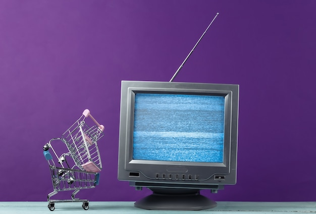 Tv shop. antenna old-fashioned retro tv with mini supermarket trolley on purple